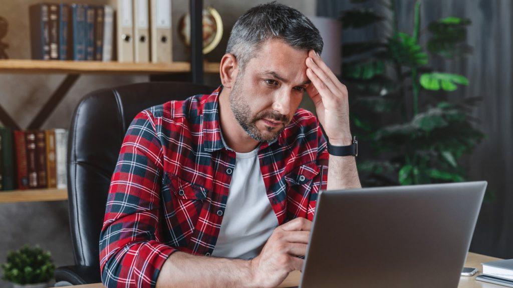 Hombre estresado frente a su computadora. concept: prestamista fraudulento en línea