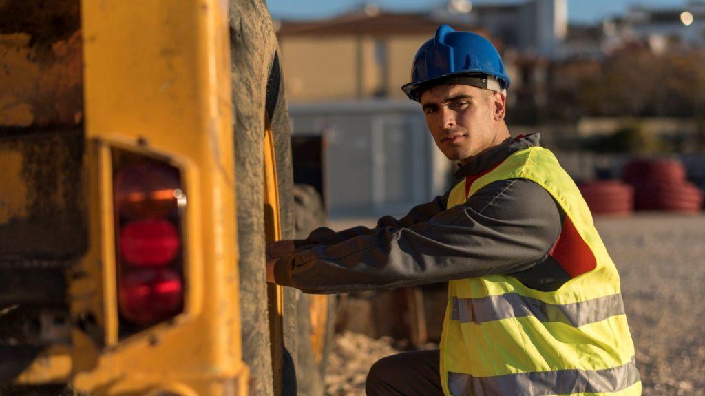 Trabajador en construcción revisando la llanta de la excavadora. concept: maquinaria de construcción