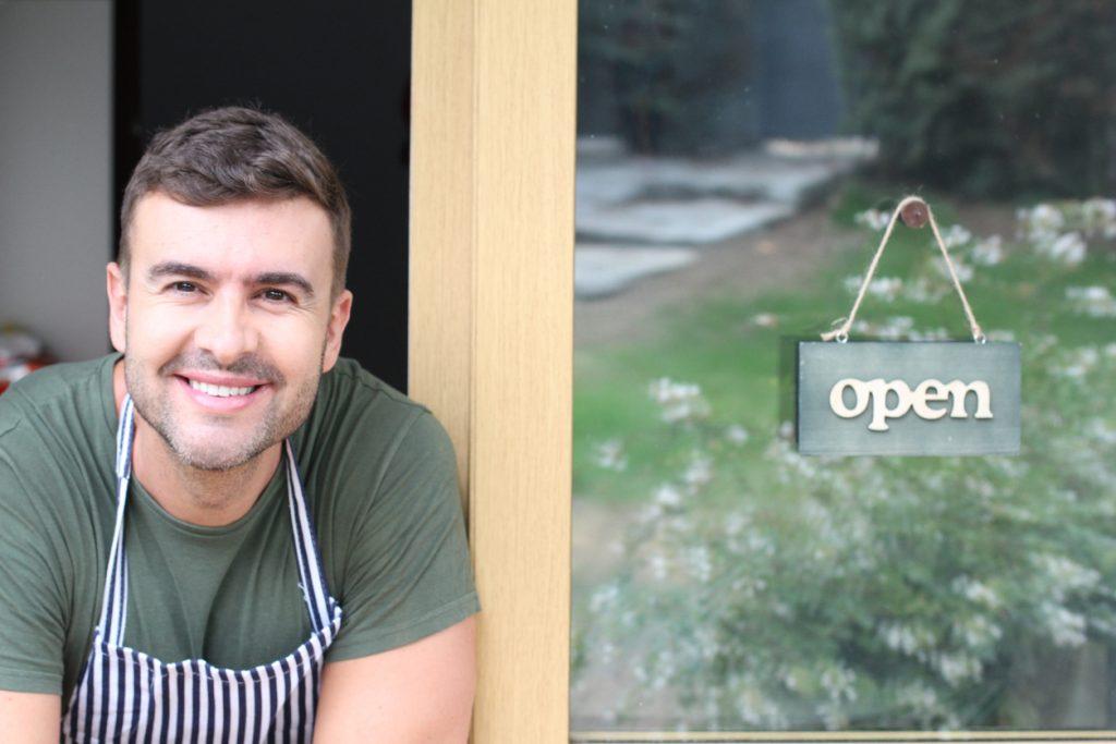 Empresario sonriendo frente a su negocio. concept: razones para obtener un préstamo