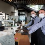 waiter in a medical protective mask serves the coffee in restaurant durin coronavirus pandemic representing new normal. concept: Restaurant Revitalization Fund