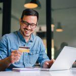 Empresario feliz mientras sostiene una tarjeta de crédito comercial