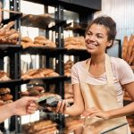 Young adult female working in bakery shop, taking wireless payment from client to improve Customer Relations