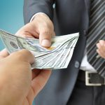 bancos que dan prestamos con itin representados por mano dando dinero